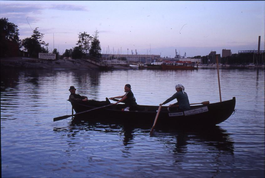 Savolaismallinen vene. Mies perässä ja naiset airoissa.